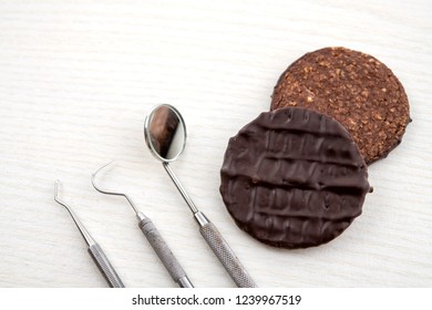 three different dental instruments and chocolate cookie on bright ground
