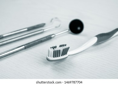 three different dental instruments and toothbrush on bright ground