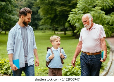 Three different generations together Affectionate dad and granddad seeing their little boy off to elementary school. Mans support, love, parentship, care concept. Back to school. First day of fall.