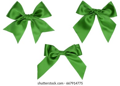 Three different green gift satin bows with tails on a white background