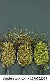 Three different green spices, herbs, condiments on black spoons and gray background