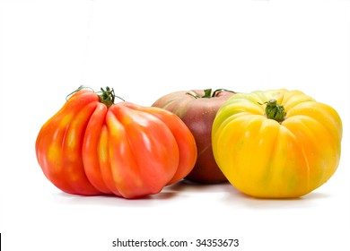 Three different kinds of richly colored heirloom tomatoes