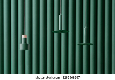 Three different metal dark green lamps are hanging on the same color folded wall background indoors. One of them has a wooden part. Closeup horizontal photo.
