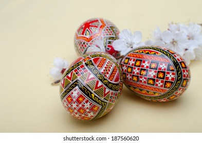 Three different painted Easter eggs with geometric motifs  and a branch with white flowers
