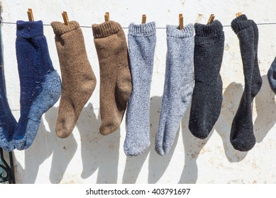 Three different pairs of socks hanging on rope with help of pegs outdoor in sunlight.