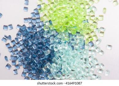 three different polymer plastic granulates on white background