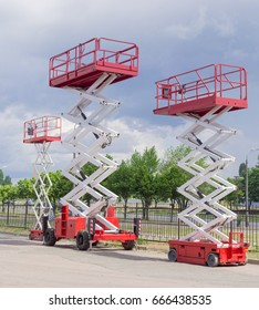 Three different red and white scissor wheeled lifts on an asphalt ground on the background of sky with clouds and trees along street
