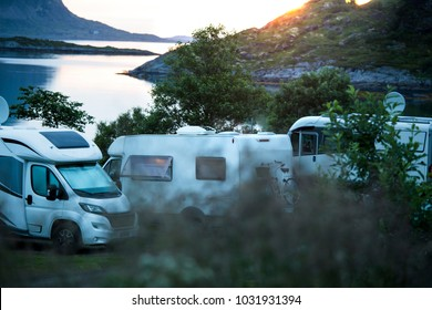 Three different RVs parked overnight nearby the sea or lake.