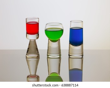 Three different shapes short glasses with red, green and blue drinks. RGB.