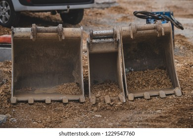 Three different sized backhoe or hoe mounts or spoons waiting to be used on a construction site. Metal spoons for backhoe on gravel.