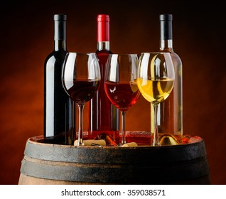 Three different sorts of wine in bottles and wineglasses. red, white and rose wine in winery on wooden barrel