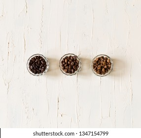 Three different varieties of coffee beans light medium dark on old vintage white background. Top view. Banner. Minimalism.