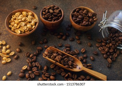 three different varieties of fresh roasted coffee beans in woden bowls on dark stone background