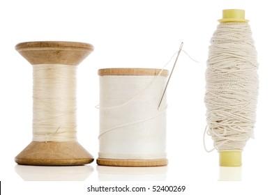 three different white spools of thread on white