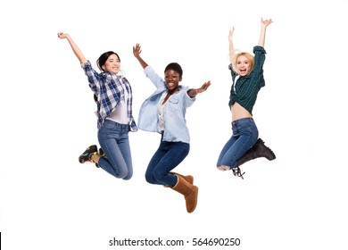 three different women, asian, caucasian and afro american jumping with happiness, isolated on white