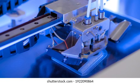 Three dimensional printing machine printing 3D plastic model at modern technology exhibition, factory - close up. Additive manufacturing, robotic automation technology concept