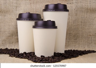 Three disposable coffee cups with plastic lid.