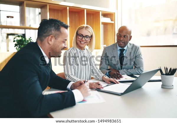 Three diverse businesspeople smiling and discussing paperwork together during a meeting around a boardroom table in a bright office