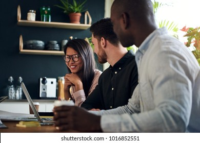 Three diverse coworkers smiling and talking together while sitting at a boardroom table during a meeting in a modern office