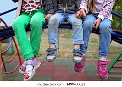 Three diverse kids sitting together on the bench in the kindergarten, happy vacation and family weekend, best friends, hand by hand, ready for adventure, outdoor lifestyle