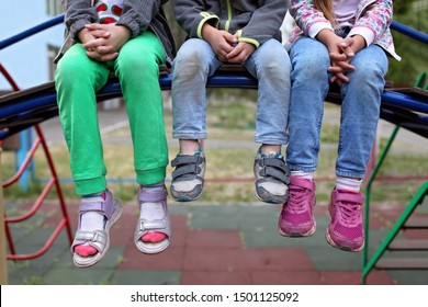 Three diverse kids sitting together on the bench in the kindergarten, happy vacation and family weekend, best friends, fashion and style, summer and autumn outdoor lifestyle