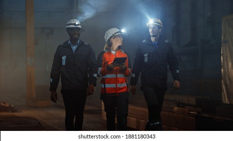 Three Diverse Multicultural Heavy Industry Engineers and Workers in Uniform Walk in Dark Steel Factory Using Flashlights on Their Hard Hats. Female Industrial Contractor is Using a Tablet Computer.