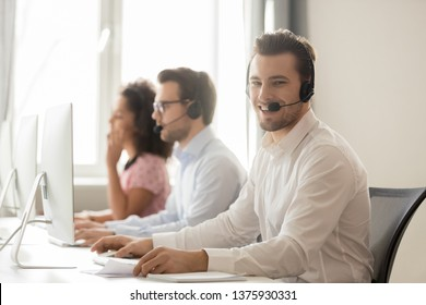 Three diverse workers service phone call center operators working wearing headset use pc, focus on smiling team member looks at camera, support everyday, opportunity to grow and develop career concept