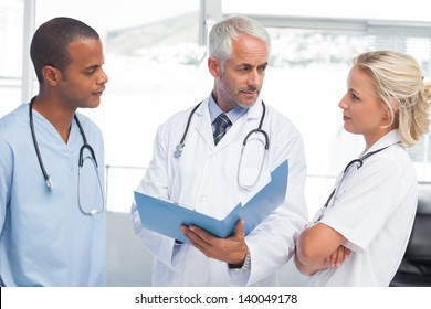 Three doctors examining a file in a bright office