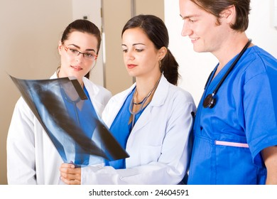 three doctors looking at patient's x-ray film