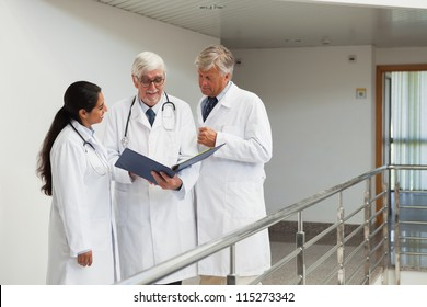 Three doctors talking in the corridor looking at patient files