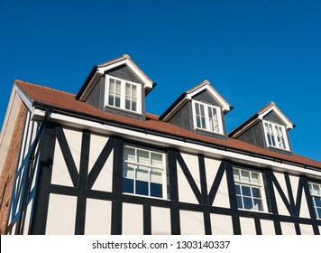Three dormer windows in the roof of a Tudor style black and white English residential home against a blue sky. The house has sash windows and soft material string pull blinds