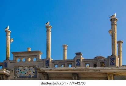 Three doves sit on top of the colums of old mosque in Turkey