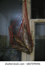 Three dried fish for beer in a red string bag hang on the window.