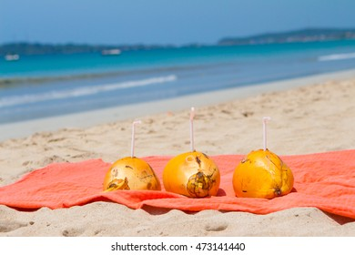 Three drinking coconut on the beach