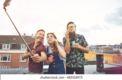 Three drunk friends taking pictures of themselves on roof with camera on selfie stick while blowing bubbles and drinking beer