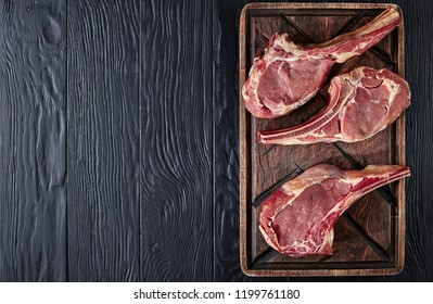 three Dry aged raw tomahawk beef steaks on an old rude wooden cutting board, close-up, flat lay, view from above, copy space