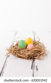 Three easter eggs in a birdnest on vintage wooden background