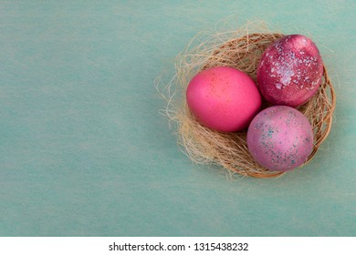 Three Easter eggs painted in shades of pink and crimson lie in a wicker basket with sisal, as in a nest. Easter concept in a rustic style.
