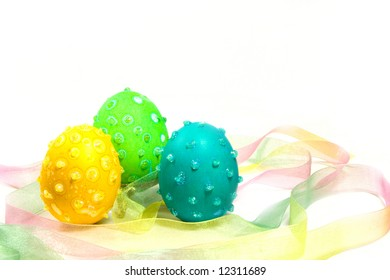 Three Easter eggs with speckles and glitter in a multicolored ribbon nest.