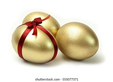 Three Easter Gold eggs with red ribbon cross and bow on white background isolated.
