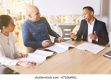 Three eclectic racially diverse business people in the middle of a very important meeting regarding the expansion of their business to reach a broader audience.