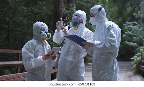 Three ecologists wearing environmental suits and exploring test tube on background of nature.