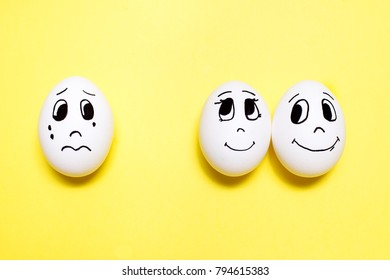 Three eggs with drawn cartoon faces on yellow background. Jealousy concept