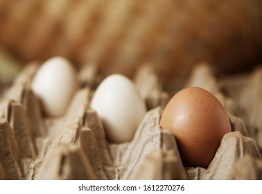 Three eggs inside a traditional egg container. Concept to describe food consumption in traditional markets.