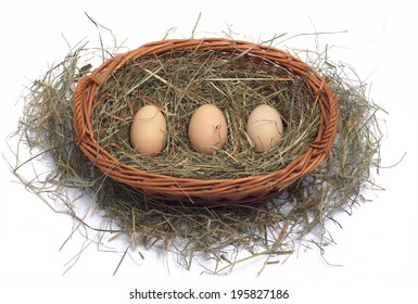 Three eggs on the hay in a wicker basket on a white background