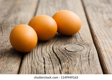three eggs on weathered wooden table