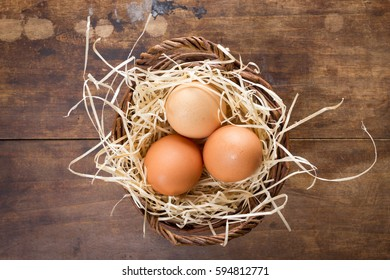 Three eggs in wicker basket on wooden background. Top view.
