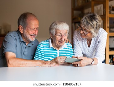 Three elderly persons using a smart phone at home, sitting on a table, smiling