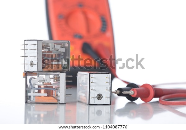Three electrical control relays and a multi-meter on white.