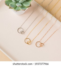 Three elegant circle gold and silver necklaces on tan background